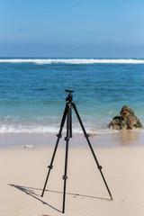Black tripod on the tropical beach of Bali island, Indonesia. Photographer lifestyle concept.