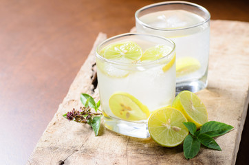 Cold lemonade with ice and fresh slice lemon in the glass on wooden plate,Healthy drink in summer