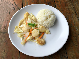 fried tofu with vegetables in white dish with thai jasmine rice on wooden background. Thai style Food. Vegetarian Food.