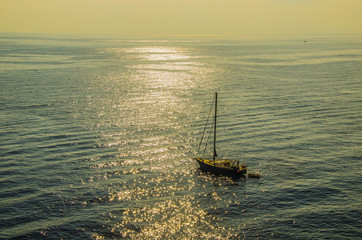 Lonely sailboat sailing on a sunset in the thyrrenean sea