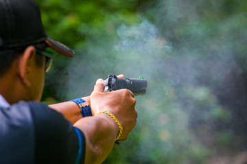 Small puff of smoke coming from a handgun after being fired