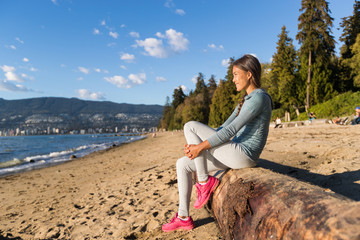 Vancouver urban lifestyle woman relaxing on Third Beach in Stanley Park, Vancouver, BC, Canada. Canadian Asian girl sitting on tree trunk at popular sandy resting area of canadian city. Fotomurales