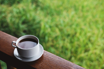 Coffee cup with saucer, on wood panel with defocus green grass lawn background