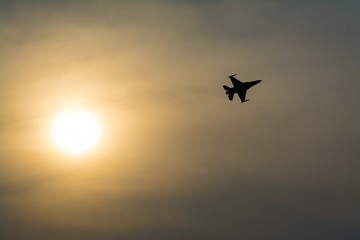 Silhouette of jet fighter at sunset