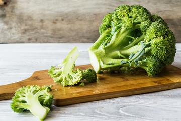 Fresh broccoli on a cutting board on a wooden background