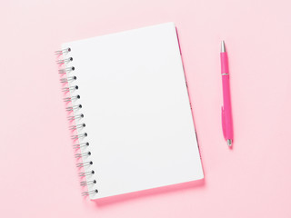 Top view of blank note paper with pen on pink pastel background. Copy space. Back to school and education concept