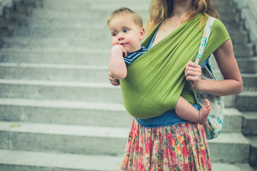 Mother with baby in sling by stairs in city