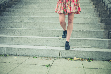 Legs of young woman walking down stairs in city
