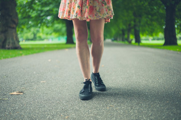 Legs of young woman walking in park