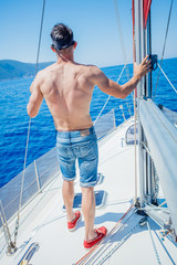 Young man sailing yacht