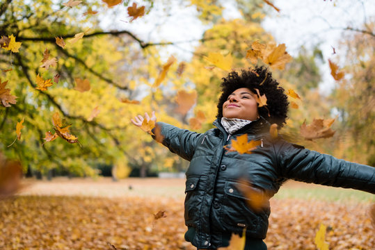 Smiling woman in park, arms outstretched.