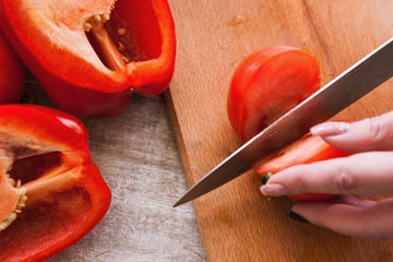 Close up picture of tomatoes and pepper cutting on wooden desk, cooking process of fresh vegetables salad