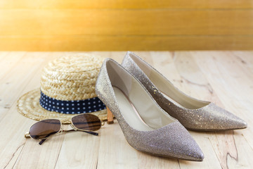 Modern style image of female fashion: straw hat, sun glasses and high heel of golden shoes.
