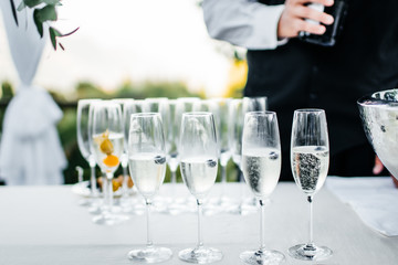 waiter and glasses of champagne on table