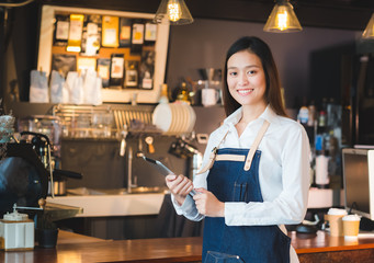 Asian female barista wear jean apron hold tablet computer coffee menu at counter bar with smile face,cafe service concept