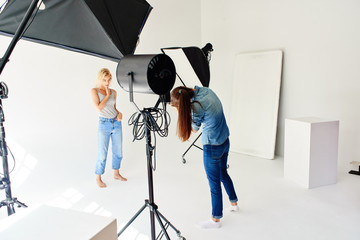 Girl photographer works in Studio with a model