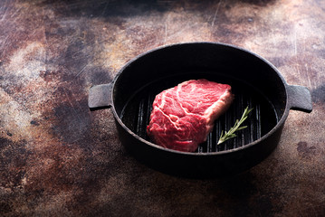 Wall Mural - Raw Beef Steak Ribeye in a cast-iron frying pan