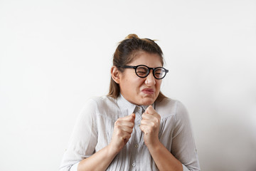 Stressed young European employee or office worker in glasses and shirt screwing her mouth in disgust, aversion or antipathy, gesturing with hands. Human emotions, feelings, attitude and reaction