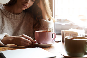 Cropped portrait of stunning young woman of European appearance drinking tea or coffee, looking thoughtful, sitting by large window at cafe table with laptop computer and mugs during work break