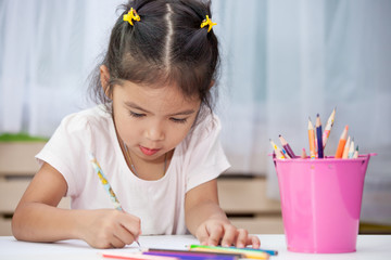 Cute asian child girl having fun to draw and paint with crayon