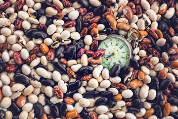 Old pocket watch partially buried in multicolored beans