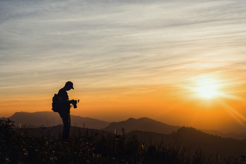 Photographer Silhouettes On Cliff Against Colorful Twilight Sky