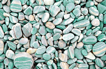 Abstract green dry round stones background. At the beach. Sea pebbles and gravel style. Top view. Close up.