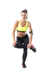 Fit pretty female athlete lifting on single leg doing squat exercise. Full body length portrait isolated on white studio background