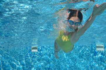 Young girl swimmer swimming freestyle in pool, under water view, sport and fitness concept