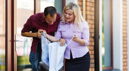 Young couple enjoying in shopping. Handsome loving couple sharing their new purchases with each after shopping. Consumerism, shopping, lifestyle concept