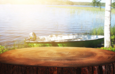 vintage wooden table in front of abstract photo of lake and boat. For product display and presentation