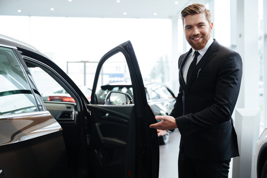 Happy smiling male dealer inviting customers