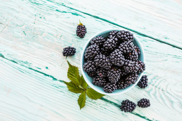 Fresh blackberries in bowl on wooden background.