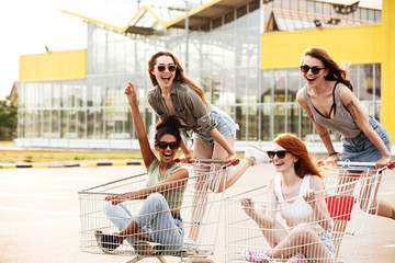 Four crazy laughing girls in sunglasses having fun