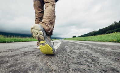 Traveler feet on the road close up image