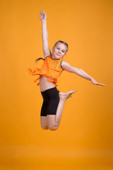 Child Girl doing sports or yoga on a yellow background in the studio