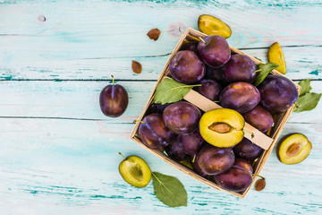 Ripe plums in a basket on a wooden table. Space for text.