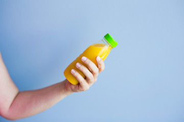 Close-up of female hand holding a bottle with juice
