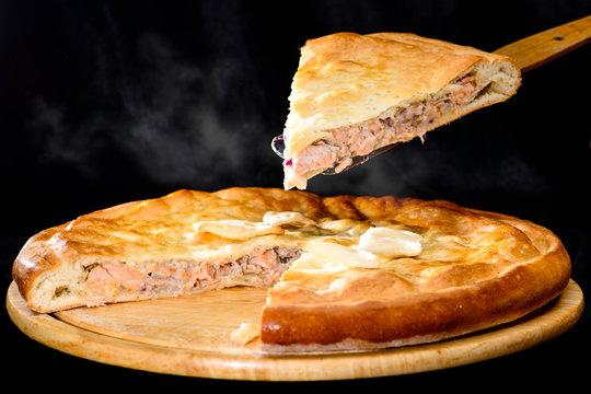 piece of tasty pie. Steaming hot round homemade delicious fish pie on wooden board, dark background