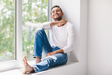 Happy smiling man relaxing on window sill