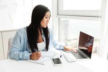Young asian woman working with laptop and taking notes