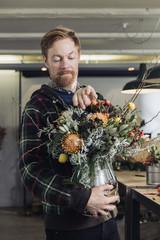 Man tweaking a flower arrangement in a silver vase
