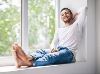 Handsome smiling man relaxing on window sill