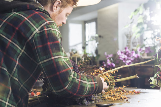Man working on flower bouquet resting on a workshop table