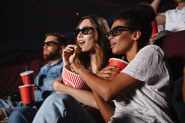 Two young women in eyeglasses watching 3d movie