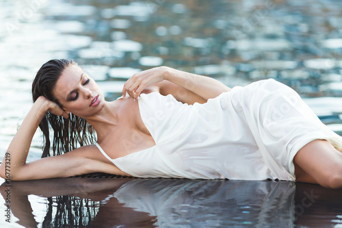 4ca14743e2567 Beautiful brunette woman in white wet dress lies in the water. Woman in the  pool