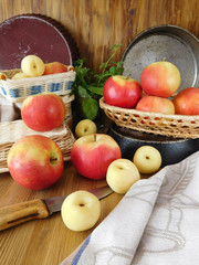 Apples and white nectarines on a wooden table and in wicker baskets