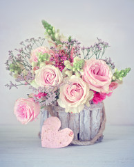Close-up floral composition with a pink roses .Beautiful bouquet for a birthday or Valentine's Day.Congratulation with a flowers in a pot decorated with a heart.
