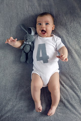 newborn to four months lying on the bed with the number four and the hare toy