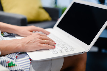 Close up of a woman hands busy typing on a laptop light background. Top side view, copy space photography. Social network communication technology